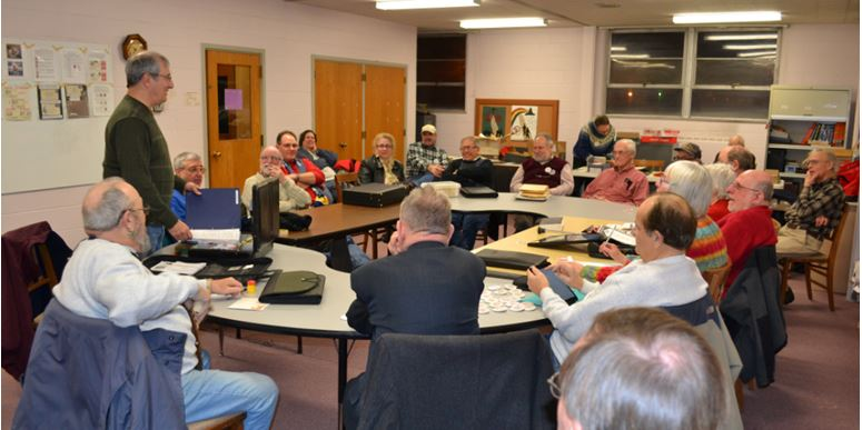 Club President Rich Spinelli (tanding) has everyone's rapt attention at the Feb. 13th meeting.  The exhibits await to be judged on the board behind Rich.