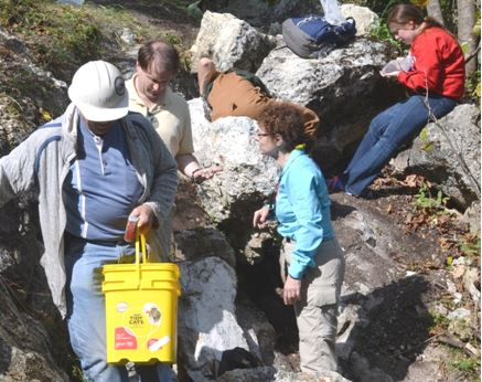 Bill Lesniak is either testing his Halloween costume and kitty litter candy bucket or he is mineral collecting at Rose Road.  SUNY-Plattsburgh professor Dr. Mary Roden-Tice (in blue) assists a student with mineral identification behind Bill.