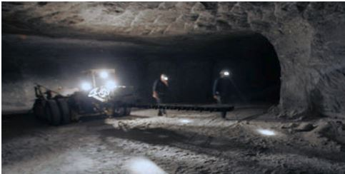 Miners work in the room and pillar mining method deployed in conventional salt mining at Hampton Corners.  The rock that has been removed here is generally 95% halite.  A sufficient number of pillars (see right) are left to hold the mine open.