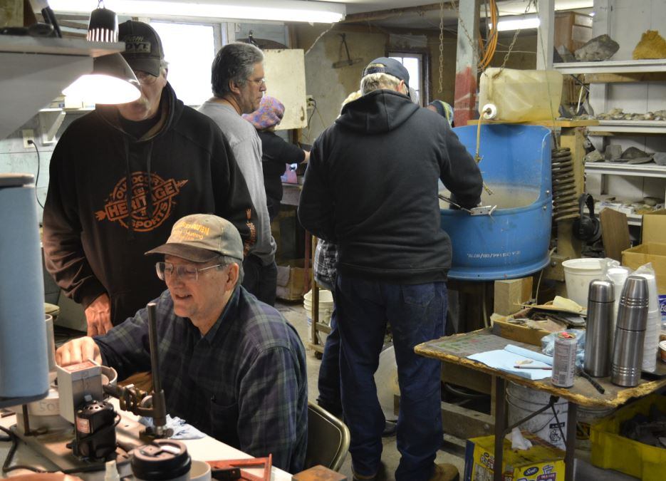 Ed instructs Gary on how to facet.  In the background Scott watches Glenn adjust a slab in the polisher