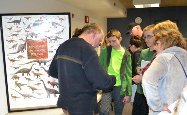 Michael Grenier discusses dinosaurs with two Walworth students and their coach.