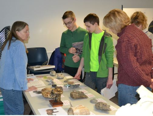 RAS President Jutta Dudley discusses her table of fossil treasures.