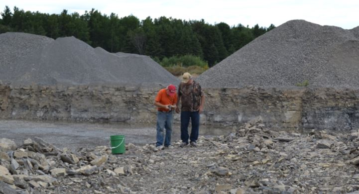 Bill Chapman shows Gary Thomas his Isotelus trilobite in Haley Quarry.  The specimen is shown in the lower left of the fossil montage below.