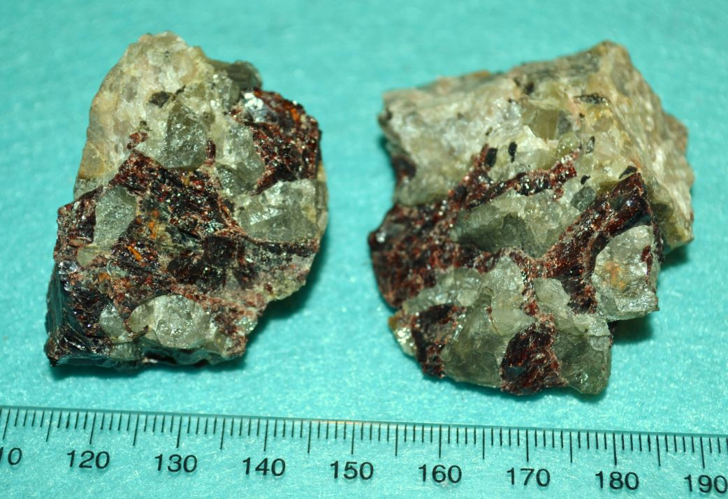 Chrysoberyl (green) and almandine garnet (red) intergrown within pegmatite boulders found on the Benson Mines dumps.