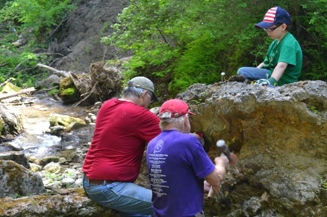 Isaac watches his dad, Ken (in red) and Bill work to extract orange stalactites exposed in a linear vug.  Or perhaps they were stalagmites; the boulder Isaac is perched upon must have fallen from the gorge walls in recent years.