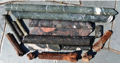 """Some of my """"prize"""" finds.  The longest Archean greenstone core with calcite veins at the top is 26"""" long and 2"""" in diameter. The rusted drill bits in the front are, well, rusted drill bits."""