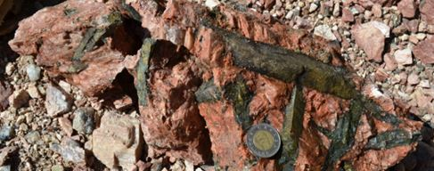 Green beryl in pink feldspar.  The Canadian $2 coin (a toonie) is 28mm in diameter, just over one inch.