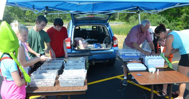 Walworth Farmer's Market:  John Murtha (green) and Henry Becker (red) assist Bill.  Note the 12 bins on the left table containing the rocks and minerals each child must locate and select for their kit.