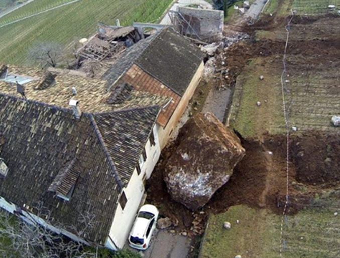 A view of the backside of the house shows an even larger boulder that stopped just short of the large estate.  Note the white van for scale.  Perhaps there was a bit of divine intervention?