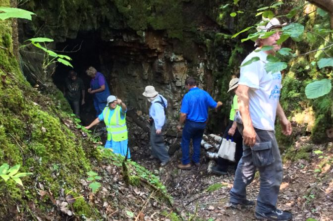 Doesn't Eva Jane look like a traffic cop at the portal into the Badger Silver Mine.  It was more than 20 degrees cooler down where Linda is standing than it was out on the dumps.  Yes that is Mario trying his best to hide behind the leaves.                                    Photo by Ashley Pollock, NPGS