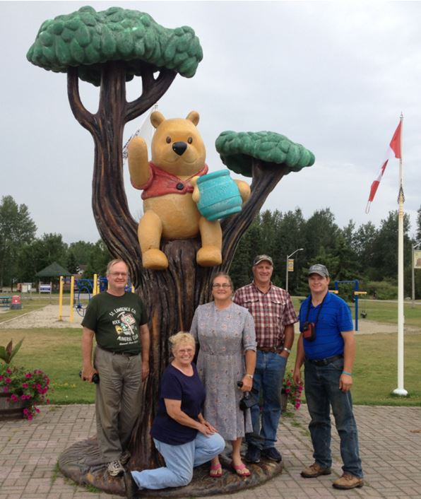 """We did see three live black bears along the roadside one our trip, but none stuck around for a group photo or for that matter a mug shot.  This guy did, however, and on the way home we got a group picture.  If you wonder why Winnie the Pooh, stories written by British author A.A. Milne, is immortalized by this """"statue"""" in Little River, Ontario, well, go look it up!"""